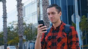Handsome caucasian man in the plaid shirt and with a backpack chatting and browsing on the mobile phone near the modern stock video