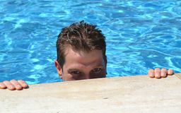 Handsome Caucasian man in the pool looking at the camera stock images