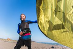 Caucasian man professional surfer standing on the sandy beach with his kite. Handsome Caucasian man professional surfer standing on the sandy beach with his kite Royalty Free Stock Photos