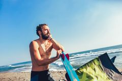 Caucasian man professional surfer standing on the sandy beach with his kite and board on the sandy. Handsome Caucasian man professional surfer standing on the Stock Photography