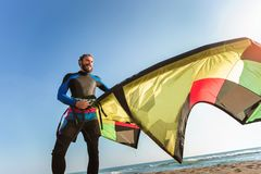 Caucasian man professional surfer standing on the sandy beach with his kite and board. Handsome Caucasian man professional surfer standing on the sandy beach Royalty Free Stock Images
