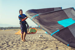 Man professional surfer standing in wetsuit with his kite Stock Photos