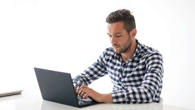 Handsome caucasian man typing on laptop and smiling. Young male model in casual shirt using computer, talking or surfing in Internet. HD video on white stock video