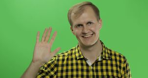 Handsome caucasian man waves and saluting on green screen chroma key royalty free stock photo