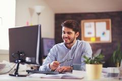 Handsome Caucasian man at work desk facing flat screen computer. Screen in office Stock Image