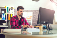 Handsome caucasian man at work desk facing flat screen computer. Screen in office Royalty Free Stock Image