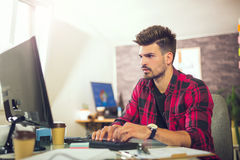 Handsome caucasian man at work desk facing flat screen computer. Screen in office Royalty Free Stock Photography