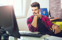 Handsome caucasian man at work desk facing flat screen computer. Screen in office Stock Images