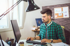 Handsome Caucasian man at work desk facing flat screen computer Stock Photos