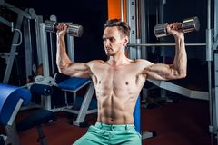 Handsome caucasian man working out at gym and doing shoulders exercises with dumbells. Royalty Free Stock Photo