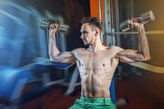 Handsome caucasian man working out at gym and doing shoulders exercises with dumbells. Stock Images