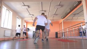 Handsome caucasian men friends train in a modern gym in a group steam training for developing endurance and burning. Excess weight, healthy lifestyle stock footage