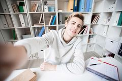 Student taking selfie. Handsome Caucasian teenage boy taking selfie and smiling joyfully while sitting alone in study room and doing homework Royalty Free Stock Photo