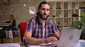 Handsome caucasian working male with nice beard is sitting at his desktop, stopping his work at computer and looking at. Camera with charming smile, indoor stock video footage