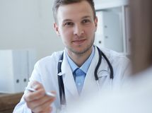 Handsome Caucasian young male doctor talking to patient at office. Healthcare and medical concept. Handsome young male doctor talking to patient at office Royalty Free Stock Image