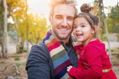 Smiling Caucasian Young Man with Mixed Race Baby Girl Outdoors royalty free stock image