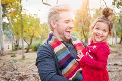 Laughing Young Man with Mixed Race Baby Girl Outdoors. Handsome Caucasian Young Man with Mixed Race Baby Girl Outdoors stock image