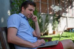 Handsome caucasian young man working on laptop and smiling while sitting outdoors. Concept of self employer. Having opportunity to work while travelling Royalty Free Stock Photos