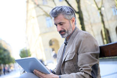 Handsome charming man websurfing on tablet in the streets Royalty Free Stock Photos