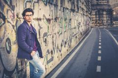 Handsome and charming young man outdoors leans against a wall in the city. Dressed in fashionable clothes and wearing eyeglasses. Coat and jeans Royalty Free Stock Photo