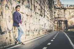 Handsome and charming young man outdoors leans against a wall in the city. Dressed in fashionable clothes and wearing eyeglasses. Coat and jeans Stock Photography