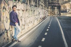Handsome and charming young man outdoors leans against a wall in the city. Dressed in fashionable clothes and wearing eyeglasses. Coat and jeans Stock Photo