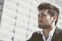 Handsome and charming young man with stylish haircut. Close-up of a handsome and charming young man with stylish haircut. Beard and intense look. Behind him the Stock Photos