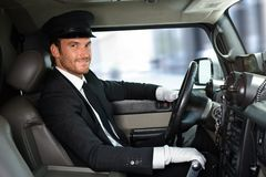 Handsome chauffeur driving limousine smiling Royalty Free Stock Photo