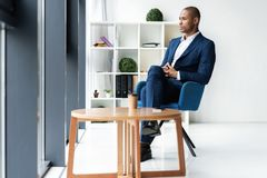 Handsome cheerful african american executive business man at the workspace office. Handsome cheerful african american executive business man at the workspace royalty free stock image