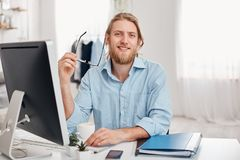 Handsome cheerful bearded young fair-haired male copywriter types information for advertisment on website, wears blue. Shirt and spectacles, sits at coworking Stock Image