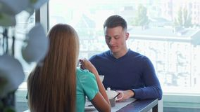 Handsome cheerful man having date with his girlfriend, enjoying breakfast together. Young happy man talking to his woman, resting at the cafe in the morning stock video footage