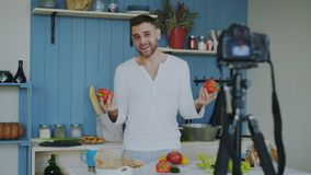 Handsome cheerful man recording video food blog about cooking on dslr camera in kitchen at home. Attractive cheerful man recording video food blog about cooking royalty free stock photos