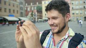 Handsome cheerful man taking photo with mobile phone in Wroclaw, Poland. Handsome cheerful man taking photo with mobile phone in some city in Europe. Young stock video footage