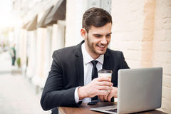 Handsome cheerful man using laptop Stock Image