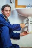 Handsome cheerful plumber repairing sink Stock Photo