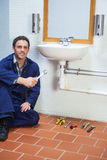 Handsome cheerful plumber sitting next to sink holding wrench Royalty Free Stock Photos