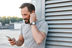 Handsome cheerful strong mature sportsman listening music with earphones using mobile phone. Image of handsome cheerful strong mature sportsman standing royalty free stock photos