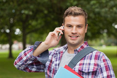 Handsome cheerful student standing and phoning Stock Photos
