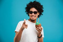 Handsome cheerful young african curly man. Image of handsome cheerful young african curly man standing isolated over blue background drinking cocktail coconut Royalty Free Stock Photo