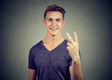 Handsome cheerful young man showing v-sign. Handsome cheerful man showing v-sign Stock Images