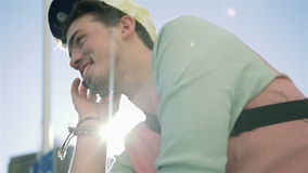 Handsome cheerful young man in the street talking on the phone in the city. stock footage