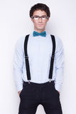 Handsome cheerful young man wearing glasses,  shirt with suspenders and a butterfly on his neck. Emotional people. Royalty Free Stock Photo