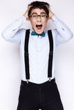 Handsome cheerful young man wearing glasses,  shirt with suspenders and a butterfly on his neck. Emotional people. Stock Image