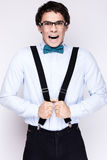 Handsome cheerful young man wearing glasses,  shirt with suspenders and a butterfly on his neck. Emotional people. Stock Images