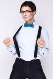 Handsome cheerful young man wearing glasses,  shirt with suspenders and a butterfly on his neck. Emotional people. Royalty Free Stock Image