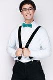 Handsome cheerful young man wearing glasses,  shirt with suspenders and a butterfly on his neck. Emotional people. Stock Photo