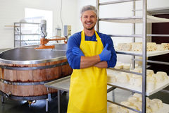 Handsome cheesemaker making curd cheese in his factory. Royalty Free Stock Photo