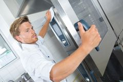 Handsome chef assistant cleaning kitchen with rag. Handsome chef assistant cleaning kitchen with a rag Stock Images