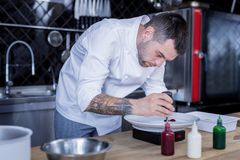 Handsome chef cooking something unusual and delicious royalty free stock photography