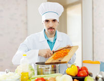 Handsome chef does veggie lunch Royalty Free Stock Photo
